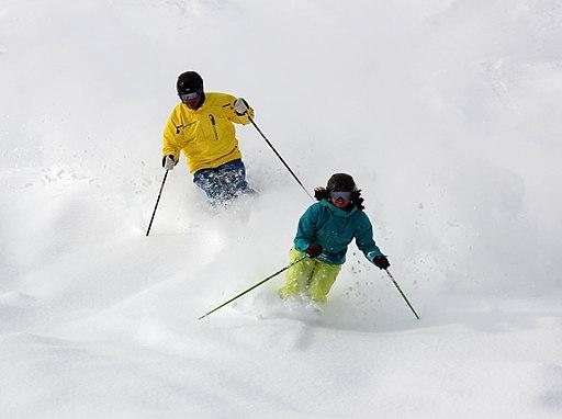 Two snow skiers ski down a mountain slope