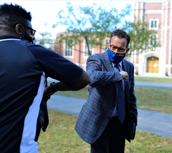Photo of Chancellor Malloy elbow touching student