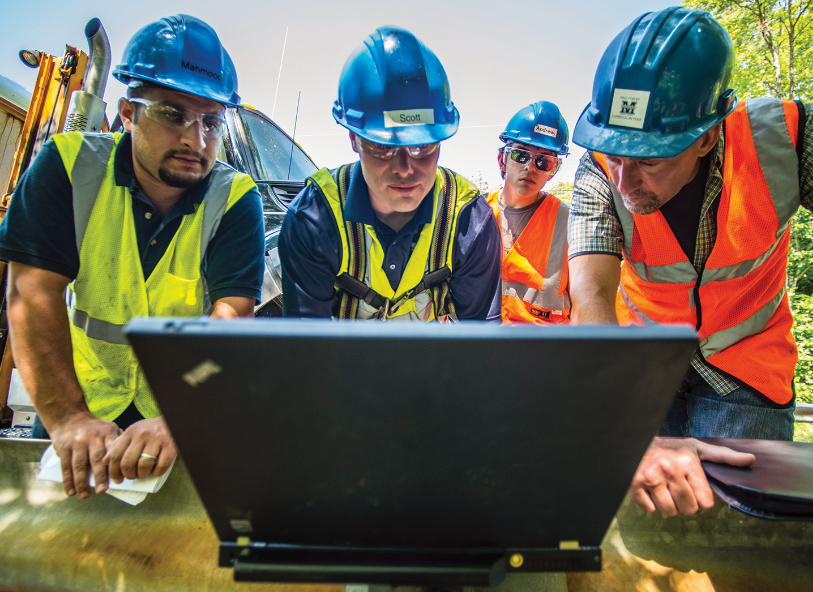 a group of engineers in hard hats and safety vests looking at laptop computer