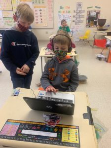 Elementary School Student uses laptop at Maine school wearing mask